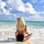 海を見てヨガをしている女性の写真