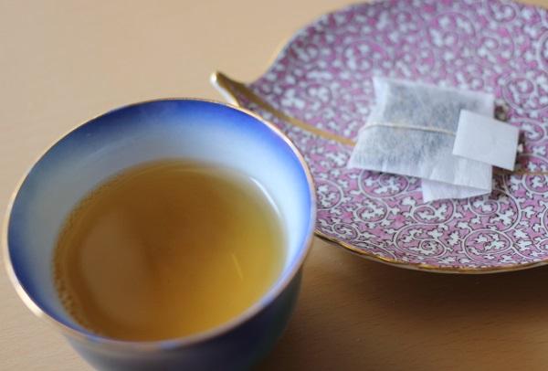 五島つばき茶のティーパックとお茶をカップに入れた写真