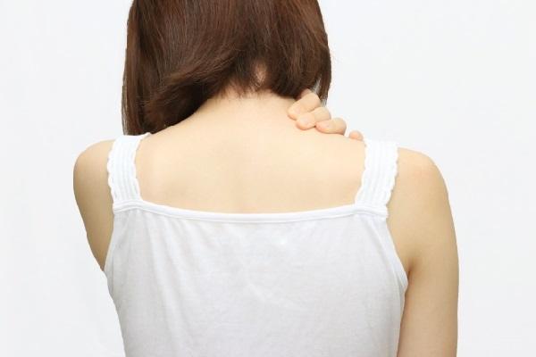 肩こりで肩をさわる女性の写真