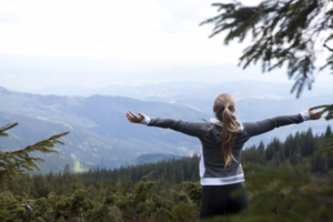 山で深呼吸している女性の写真