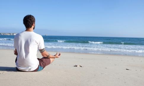 海を見て瞑想する男性の写真