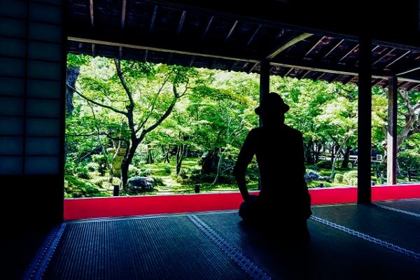 お寺で瞑想してる男性の写真