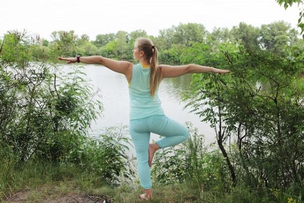 湖畔でバランスポーズをする女性の写真