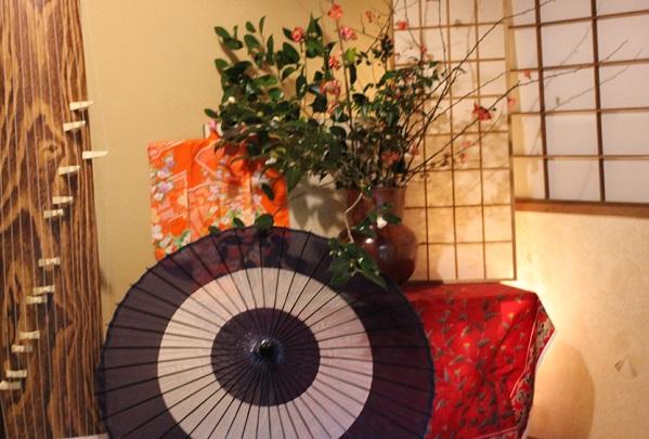茶室への入り口、琴や和傘、生け花の写真