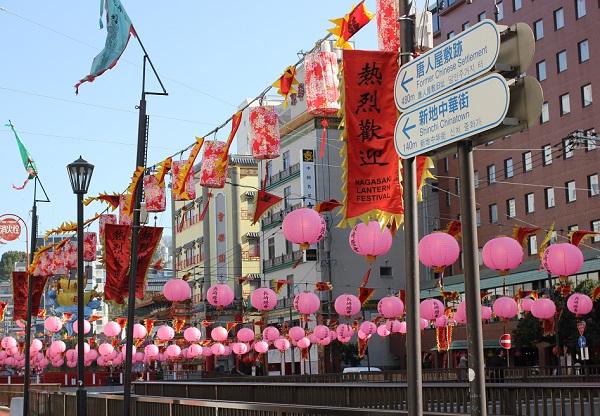 新地中華街会場への案内板と、銅座川にかかるピンクのランタンの写真