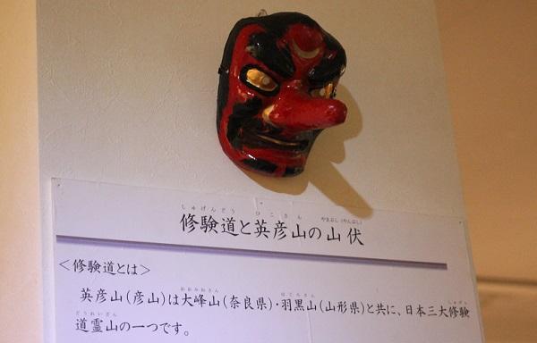 英彦山の花駅の山伏文化財室にある天狗のお面と英彦山の説明文章の写真