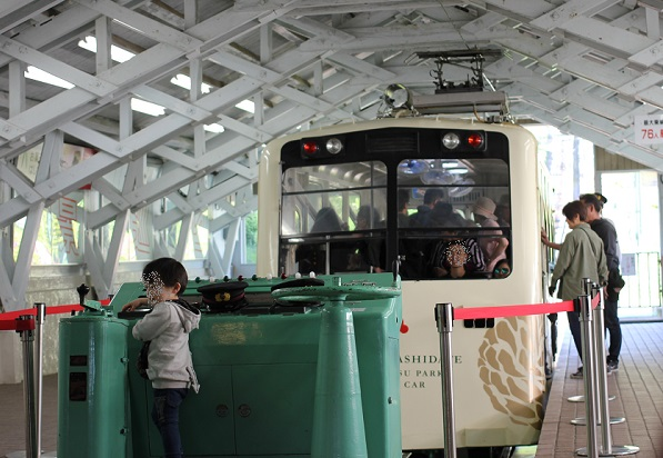 傘山公園行きのケーブルカー、人々が乗車している写真