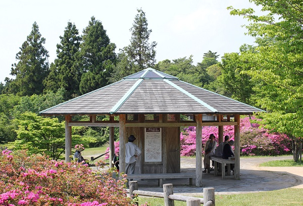 宝原つつじ公園の中央広場にある屋根付きベンチと案内看板の写真