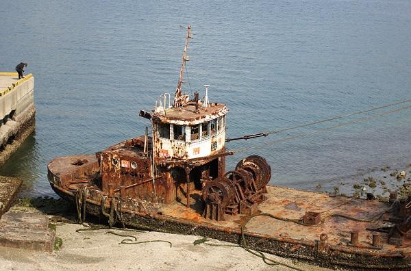 鼠島、サビついた廃船と釣りをしている男性の写真