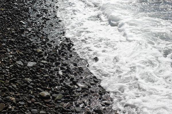 潮井崎公園の海岸、黒っぽい小石と打ち寄せる波の様子の写真