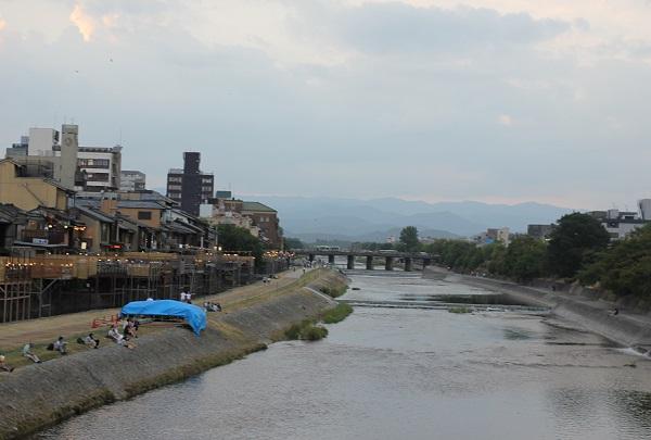 夏の夕暮れ時の鴨川の様子、川床や夕涼みをしている人々の写真