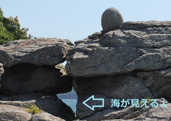 堂崎鼻の岩と岩の上にある丸い石、海が臨めるすき間の写真
