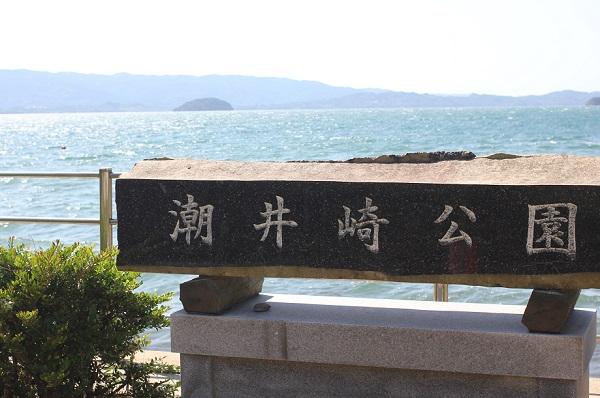 大村湾を背景にある潮井崎公園の石の看板の写真
