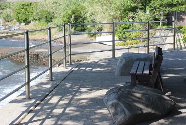 潮井崎公園、大村湾を一望できる海の側にある大きな木の下にあるベンチの写真