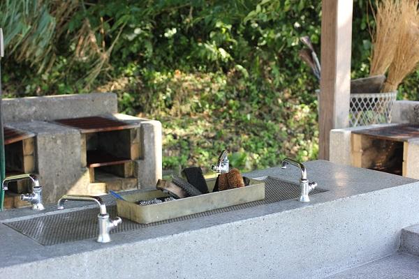 潮井崎公園のキャンプ場広場にある炊事棟の炊事場と野外炉の写真