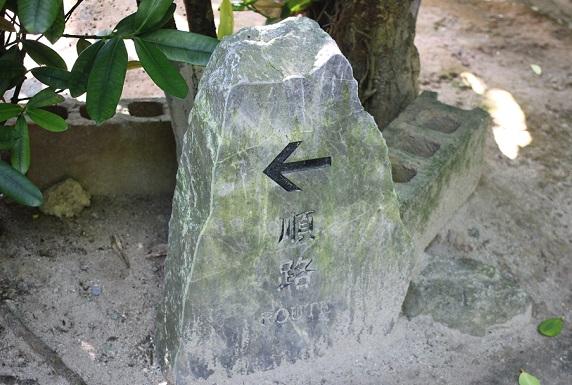 フクギの並木道、順路と書いてある案内石の写真