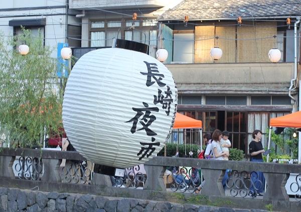 夕方の長崎夜市、中島川の上に飾られてる大提灯の写真