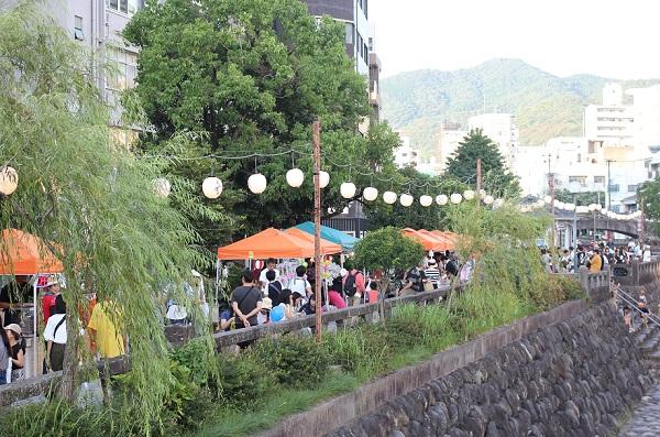 長崎夜市の夕方、川沿いの出店の様子の写真