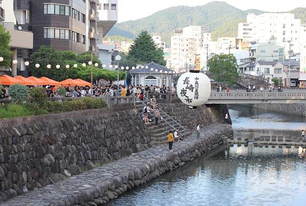 夕方の長崎夜市、オレンジ色の屋根の出店と中島川の様子の写真