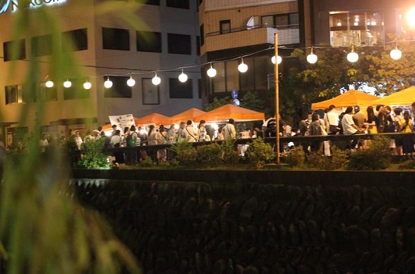 夜の長崎夜市の様子、柳の向こうライトアップした中島川と屋台の写真