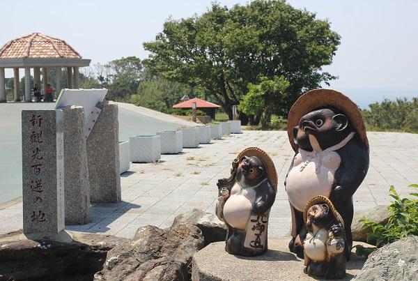 崎戸、新観光百選の地の石碑とタヌキの置物の写真