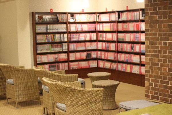 湯快リゾート、館内にある漫画の本棚とイスの写真