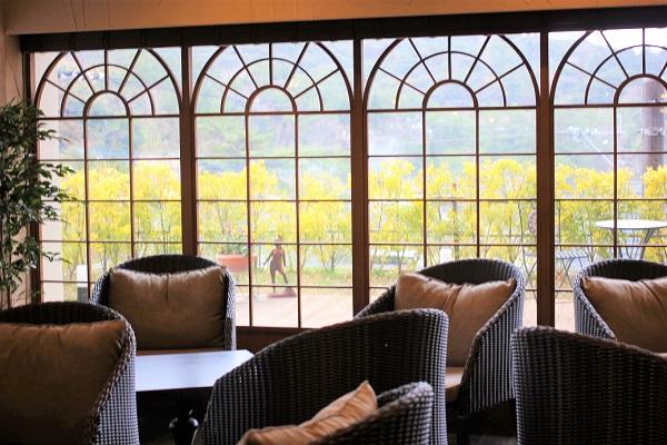 湯快リゾート、1階にあるテラス、椅子やテーブルがある写真