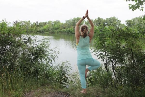 湖の近くで立ち木のポーズをしている女性の写真