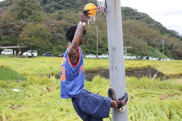 鬼木の棚田の案山子、電信柱のゴールポストにジャンプしてシュートしてる(バスケット)様子の案山子