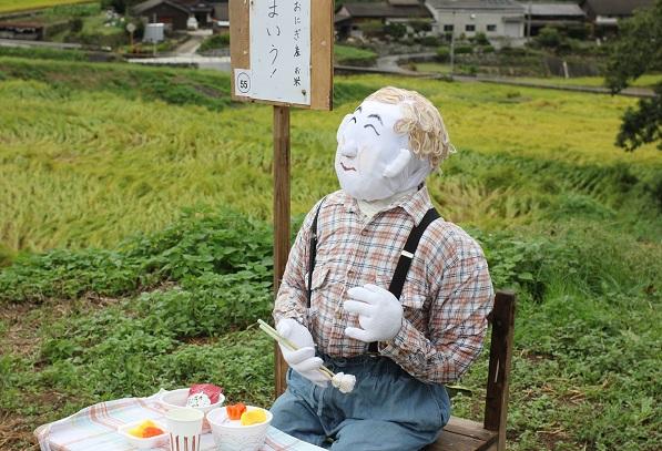 鬼木の棚田の案山子、まいうの看板と美味しそうに食事してる案山子の写真