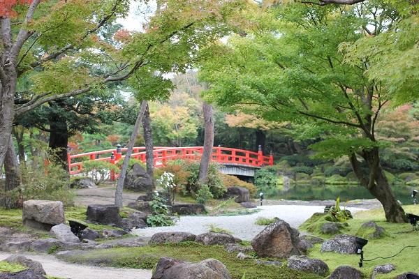 由志園の庭園、築山へ向かう赤い橋の写真
