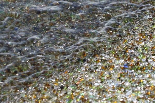 波打ち際、海水とガラスの砂浜の写真
