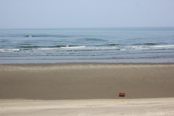 吹上浜海岸の海、砂浜、小さく見えるドラム缶の写真