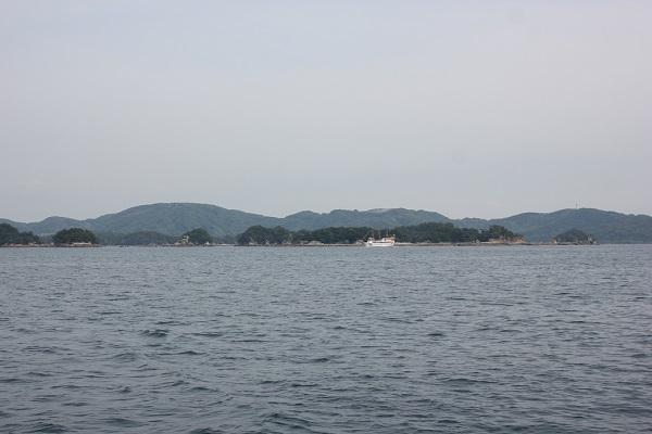 九十九島の海、遠くに見える遊覧船や島の様子の写真