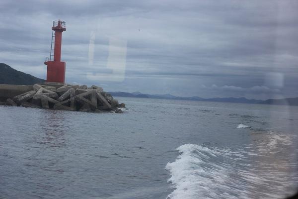 シーガルの窓から見える景色、赤い灯台と白い波の写真